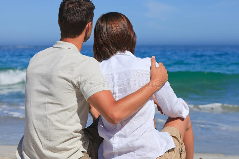 Lovely couple at the beach. Young lovely couple at the beach royalty free stock photography