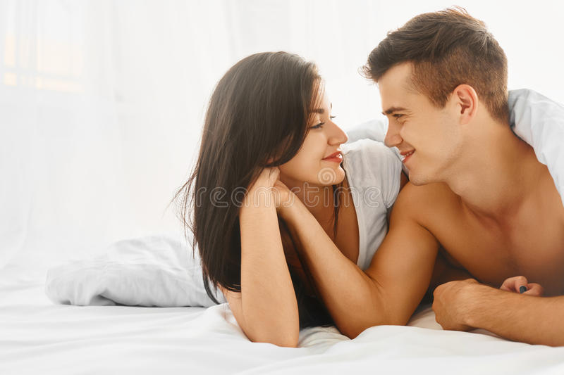 Lovely couple in bed. Young lovely tender couple enjoying morning lying in bed in their bedroom. Love and relationships concept royalty free stock images