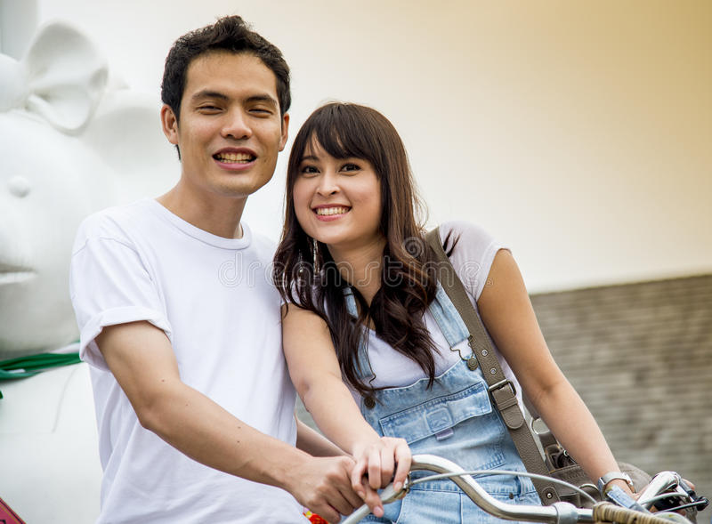 Lovely couple with bicycle in the amusement park stock photos