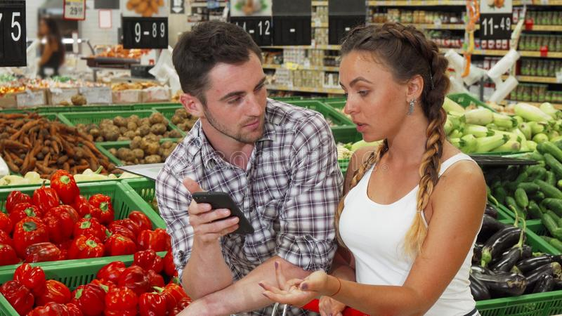 Lovely couple checking list on their smart phone while shopping for food. Handsome men and his attractive girlfriend using smart phone while doing groceries stock image