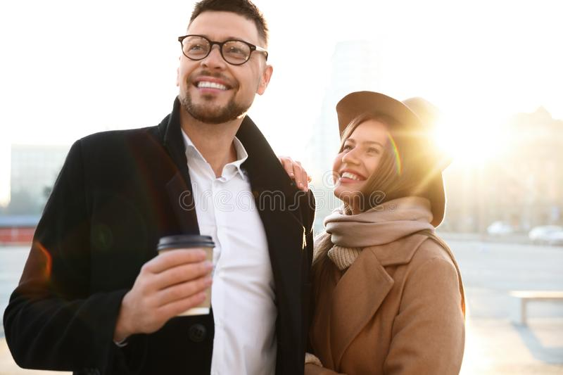 Lovely couple with cup of coffee on street in morning. Lovely couple with cup of coffee on city street in morning stock image