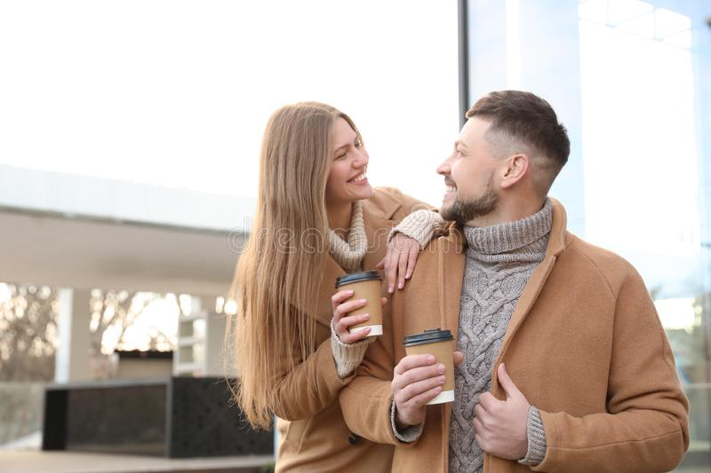 Lovely couple with cups of coffee on street in morning. Lovely couple with cups of coffee on city street in morning stock photography