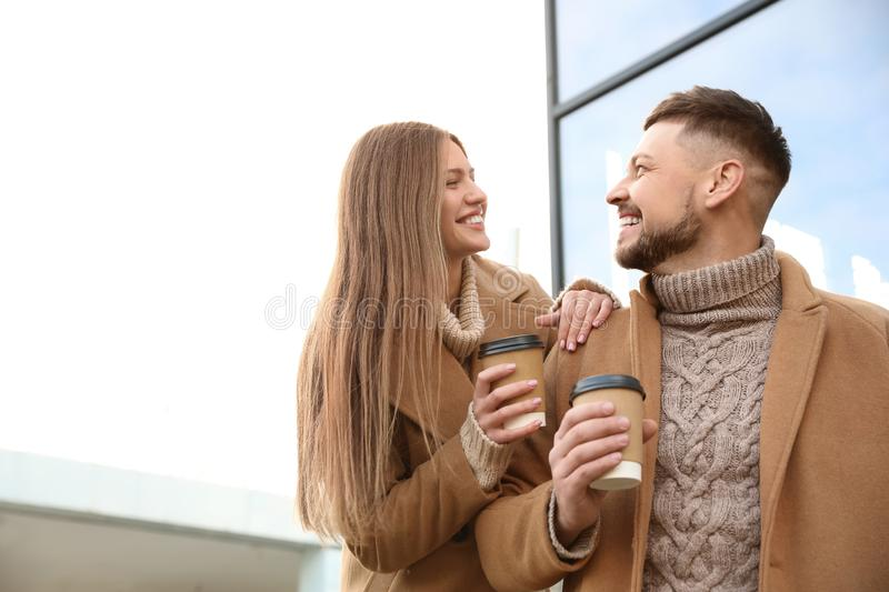 Lovely couple with cups of coffee on street in morning. Lovely couple with cups of coffee on city street in morning royalty free stock images
