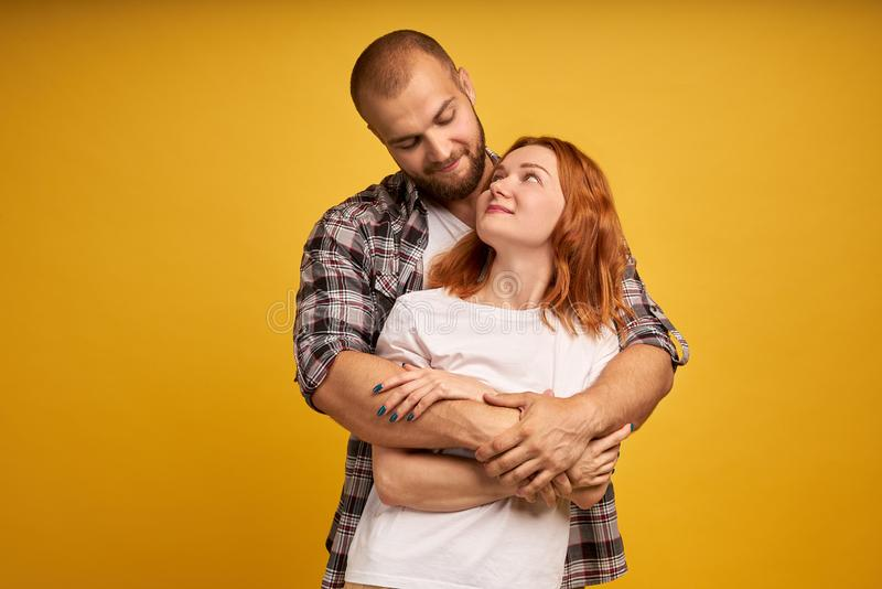 Lovely couple have warm cuddle, pose for family portrait, smile joyfully, have good relationships. Affectionate brother embraces royalty free stock photo