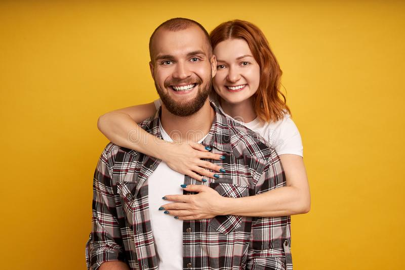 Lovely couple have warm cuddle, pose for family portrait, smile joyfully, have good relationships. Affectionate brother embraces royalty free stock photos