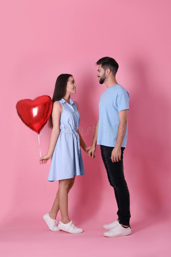Lovely couple with heart shaped balloon on background. Valentine`s day celebration royalty free stock images