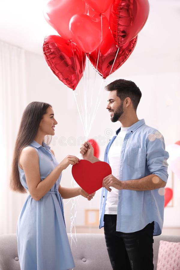Lovely couple with heart shaped balloons in room. Valentine`s day celebration royalty free stock image