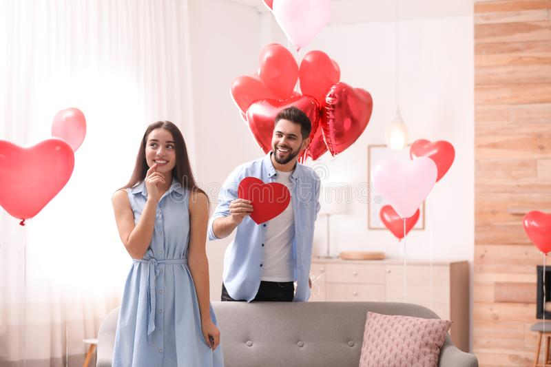 Lovely couple with heart shaped balloons in room. Valentine`s day celebration. Lovely couple with heart shaped balloons in living room. Valentine`s day stock photo