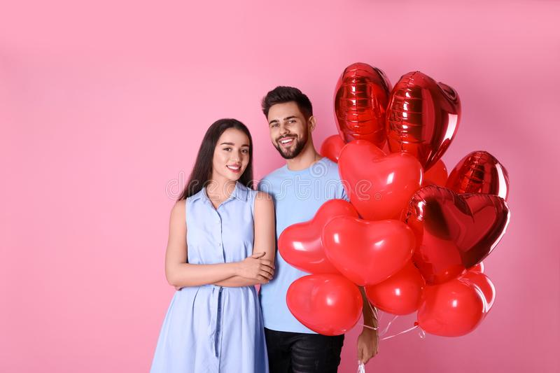 Lovely couple with heart shaped balloons on background. Valentine`s day celebration. Lovely couple with heart shaped balloons on pink background. Valentine`s day royalty free stock photography