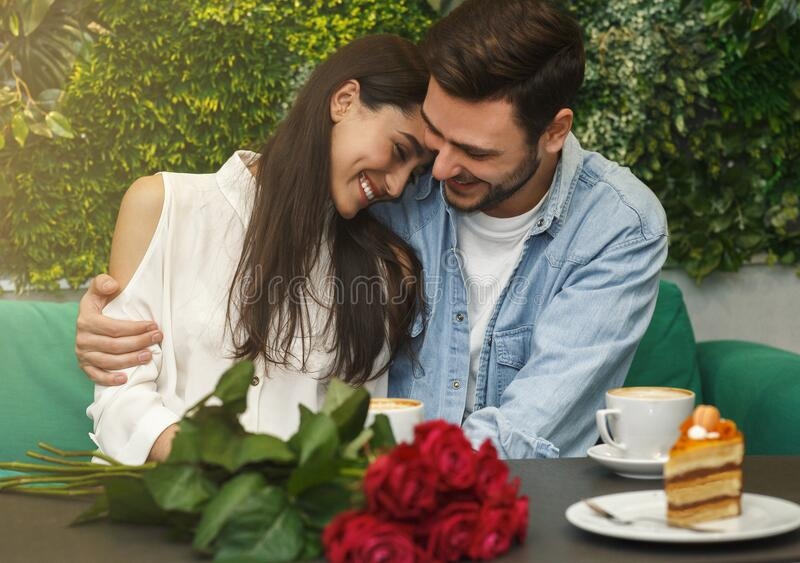Lovely Couple Hugging Having Romantic Date Sitting In Cafe royalty free stock photo