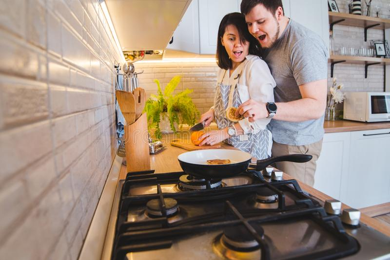 Lovely couple hugging on the kitchen while cooking breakfast royalty free stock photography