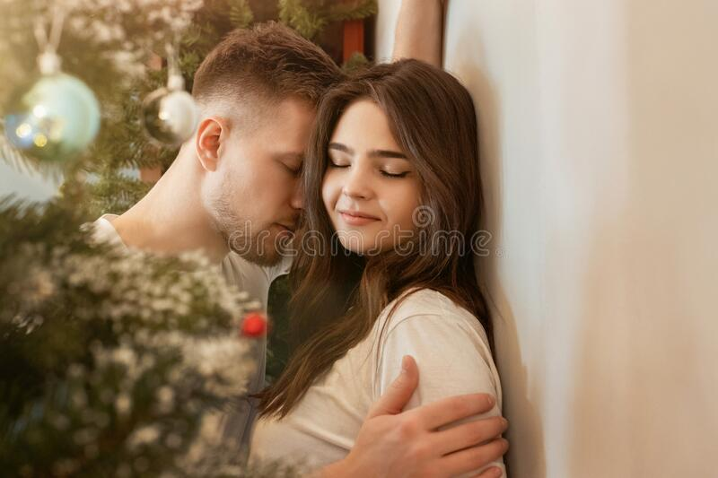 Lovely couple husband hugging his beautiful wife with passion standing in room decorated for celebrating new year festive mood. Love story stock image