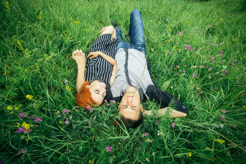 Couple lie on the grass royalty free stock image
