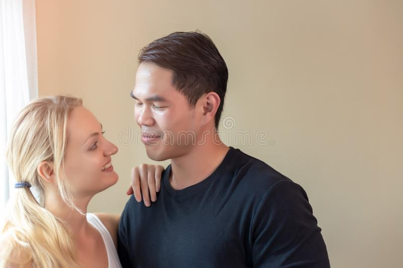 Lovely couple or lovers looking at eyes each other with smile faces. Handsome young asian guy and beautiful young caucasian woman stock photos
