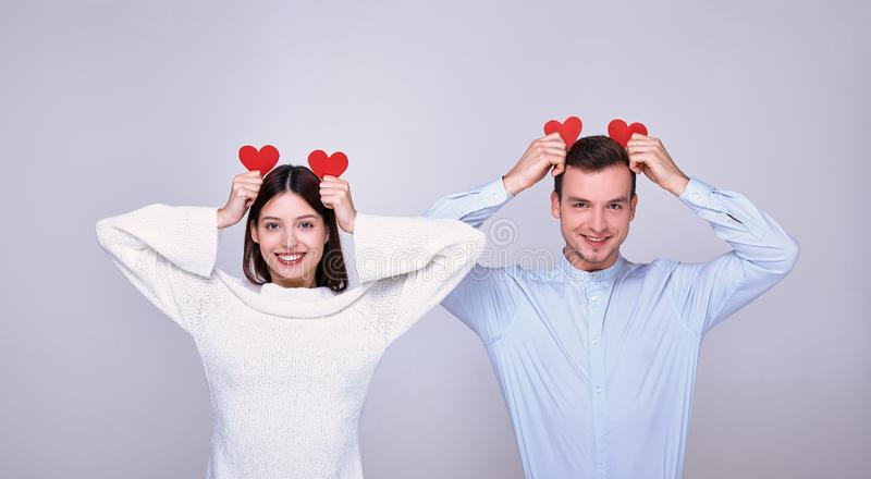 A lovely couple of lovers with a playful mood on St. Valentine`s Day both holds two red cardboard hearts stock images