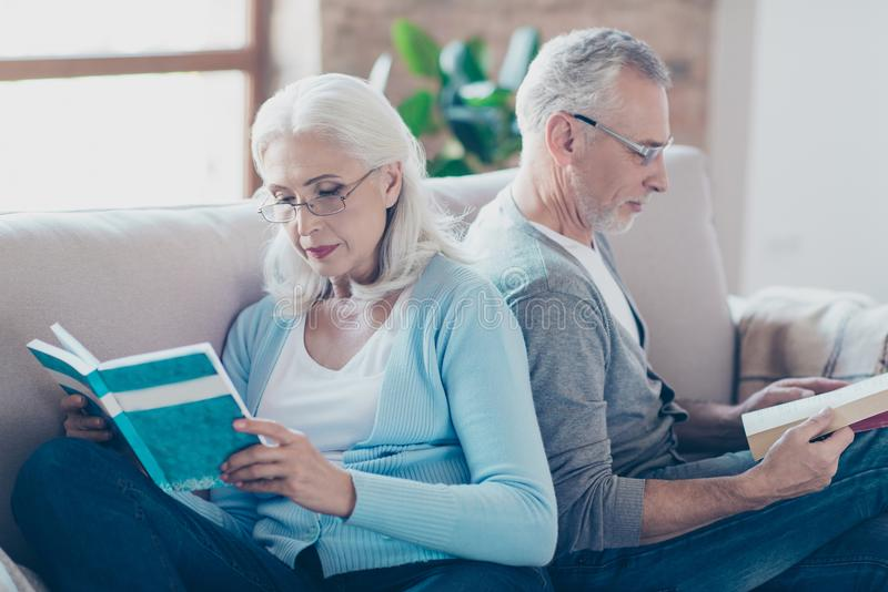 Lovely couple of old wife and husband are reading book with glasses, sitting on a couch at nursing home royalty free stock photo