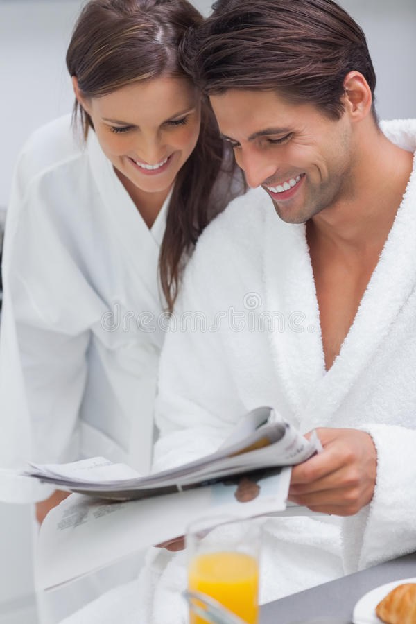 Lovely couple reading newspaper stock images
