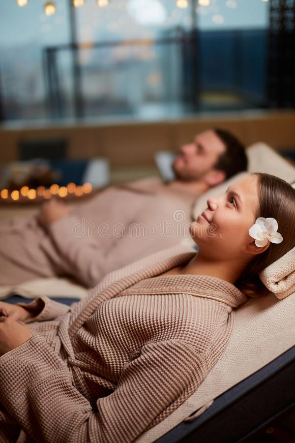Lovely couple relaxing on loungers in Spa salon. Young caucasian couple relax on loungers in spa center, taking rest together, lying around candles stock photography