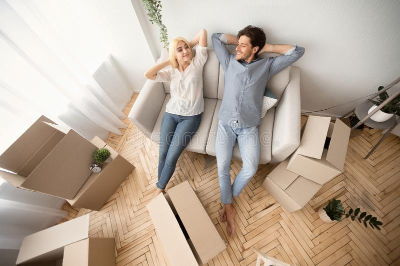 Lovely Couple Relaxing On Sofa In New Flat, Above View. Cheerful Couple Relaxing On Sofa Among Boxes After Moving New House. Above View, Free Space stock image