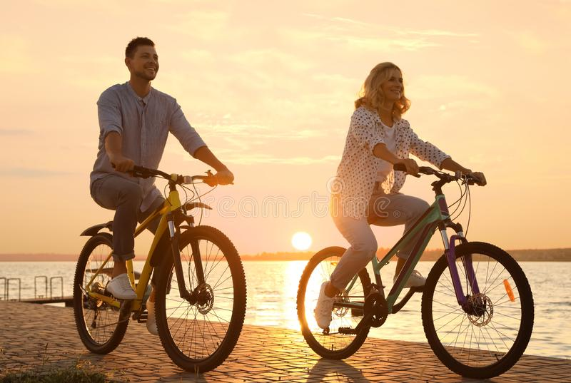 Lovely couple riding bicycles on embankment. At sunset stock photos