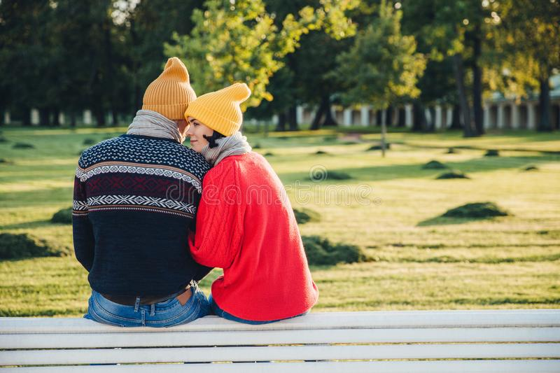 Lovely couple sit on bench together, wear warm clothes and knitted hats, embrace each other, express love and good relationship, e stock images