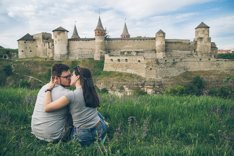 Lovely couple sits on ground in front of old castle stock photo