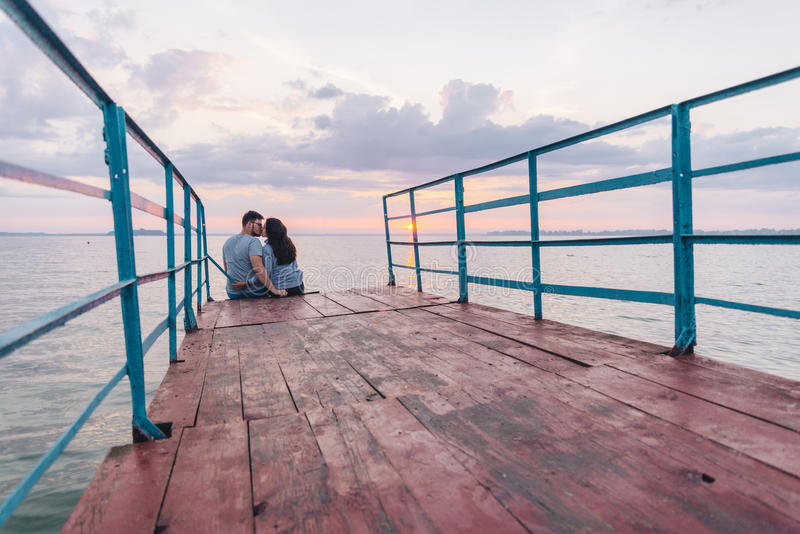 Lovely couple sitting on the pier and looking on sunrise royalty free stock photography