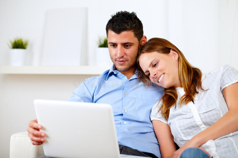 Download Lovely Couple Smiling And Reading On Laptop Stock Photo - Image: 25502734