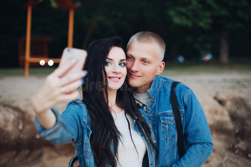 Lovely couple walking in park and taking selfie together stock photos