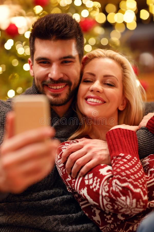 lovely couple in warm sweaters taking selfie picture with smartphone at home. royalty free stock images