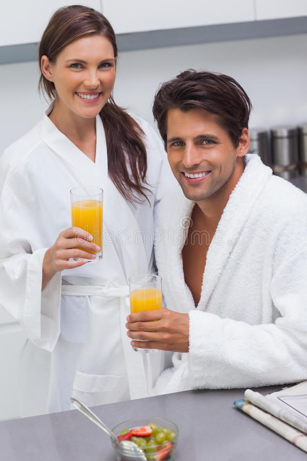 Lovely couple wearing bathrobes and holding glass of orange juice stock photography