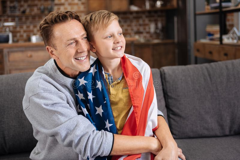 Happy father hugging his son in US flag. Lovely cuddles. Happy loving father sitting on the sofa and cuddling his beloved little son wearing a US flag on the royalty free stock image