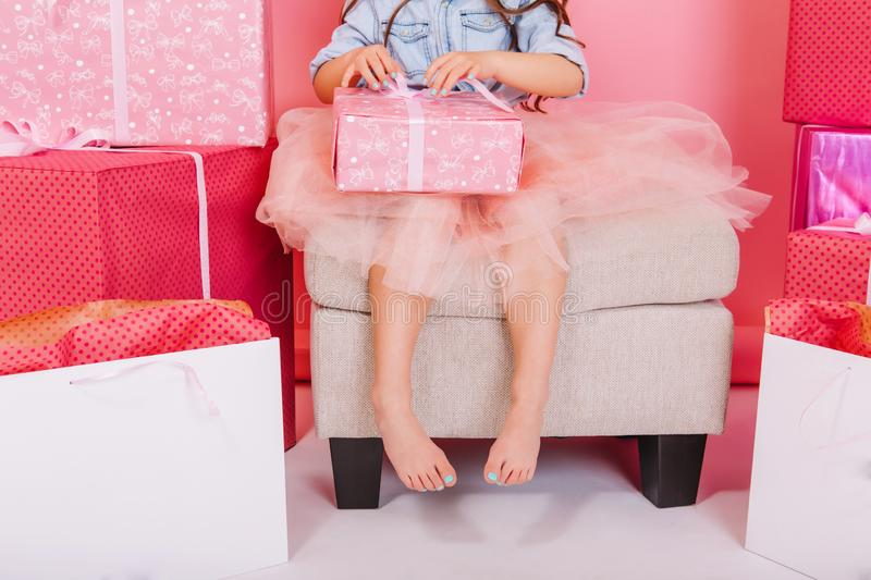 Lovely cute image of birthday kid opening present on knees suround big giftboxes, balloons on white floor. Amazing. Little princess in tulle skirt celebrating stock image