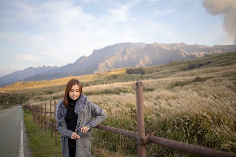 Lovely cute japanese girl standing on Aso active volcano background with smoke at Mount Aso Nakadake, Kumamoto. Kyushu, Japan photo grain some noise for film royalty free stock photos