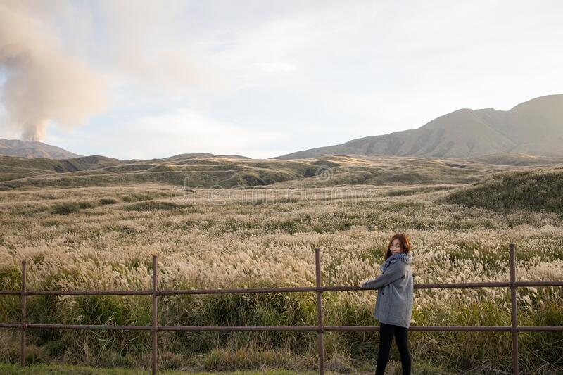 Lovely cute japanese girl standing on Aso active volcano background with smoke at Mount Aso Nakadake, Kumamoto. Kyushu, Japan photo grain some noise for film stock images