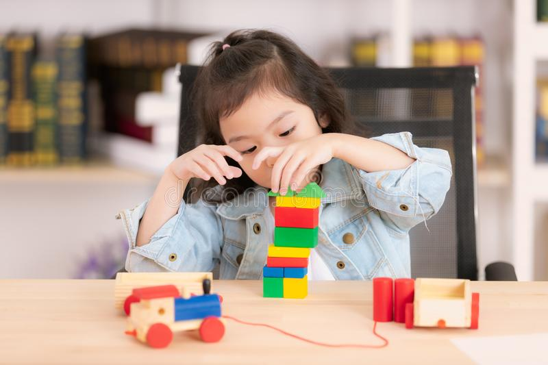 Lovely cute little Asian girl in jeans shirt playing wood block stock images