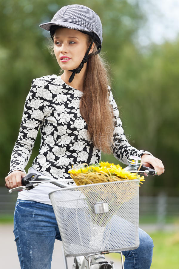 Lovely cyclist. Young and lovely cyclist riding retro bicycle with basket and bunch of flowers stock image