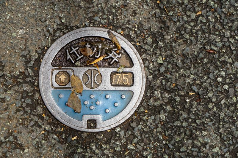 Lovely design circular public manhole with sign and symbol on paved road cover by yellow leaves, Kurokawa onsen town royalty free stock photo