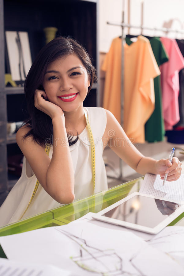 Lovely designer. Vertical portrait of a young lovely designer at the workplace smiling and looking at camera stock photo