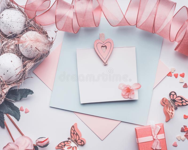 Lovely Easter greeting card on pastel color , mock up with eggs ribbon, gift box and decoration. Top view stock photos