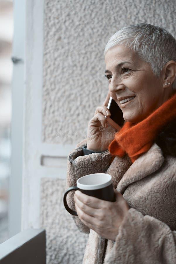 Happy senior woman having a pleasant phone call royalty free stock photos
