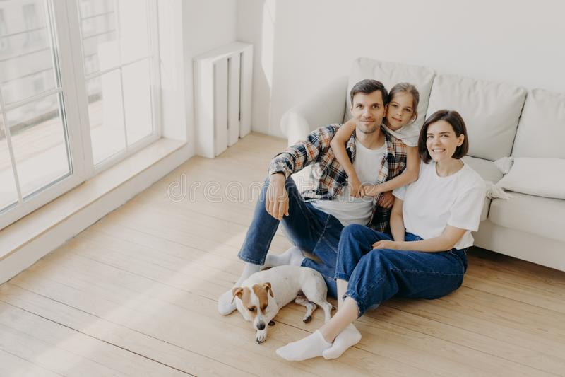 Lovely European family of father, mother and their daughter sit on floor near sofa in spacious white room, pedigree dog lies near stock photos