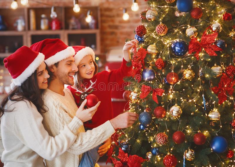 Lovely family decorating xmas tree with bubbles at home stock photography