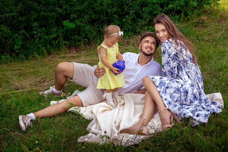 Lovely family having fun at the park. Parents with daughter relaxing outdoors stock image