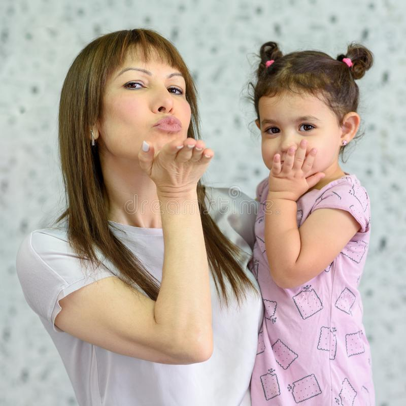 Mom and daughter smile looking at camera blowing kiss, small kid spend time with young grandma, communicate via internet royalty free stock photos