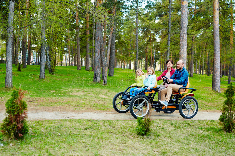 Lovely family riding quadricycle pedal car stock images