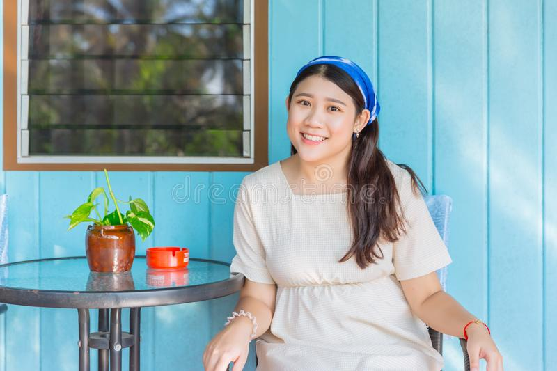 Lovely fat girl plus size cute teen smiling portrait sitting smile at front wooden home background. Lovely fat Asian girl plus size cute young teen smiling stock photo