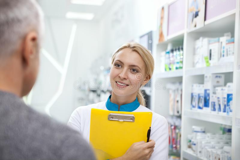 Lovely female pharmacist helping her client. Happy female pharmacist smiling cheerfully to her senior client, working at the drugstore. Beautiful chemist helping royalty free stock photo