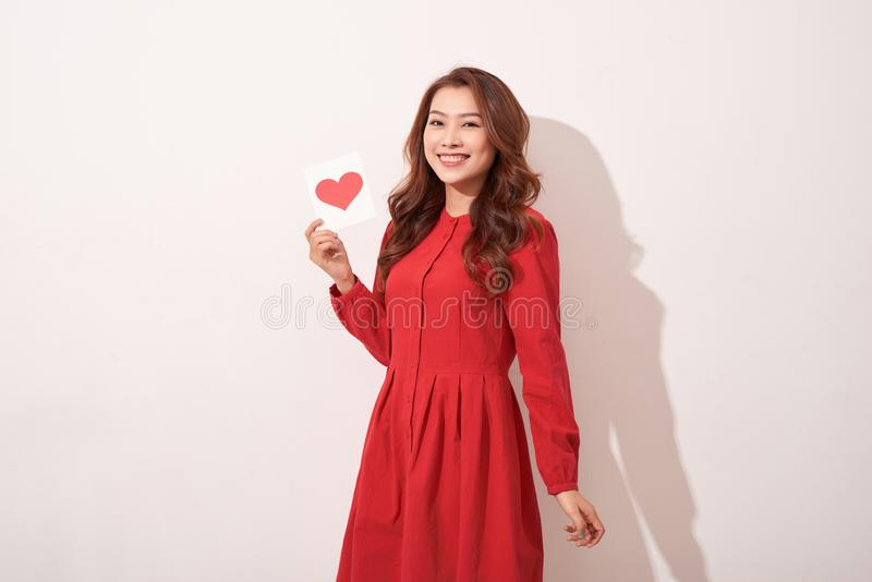 Lovely female with red heart isolated on gray background, celebration of Valentine day, romantic feelings, harmony and love stock photo