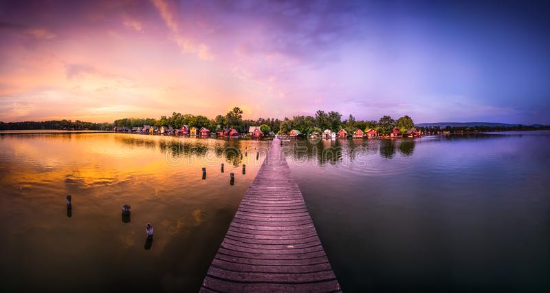 Lovely fishing lake. A lovely fishing lake with cozy wooden houses at sunset from Tata, hungary royalty free stock image